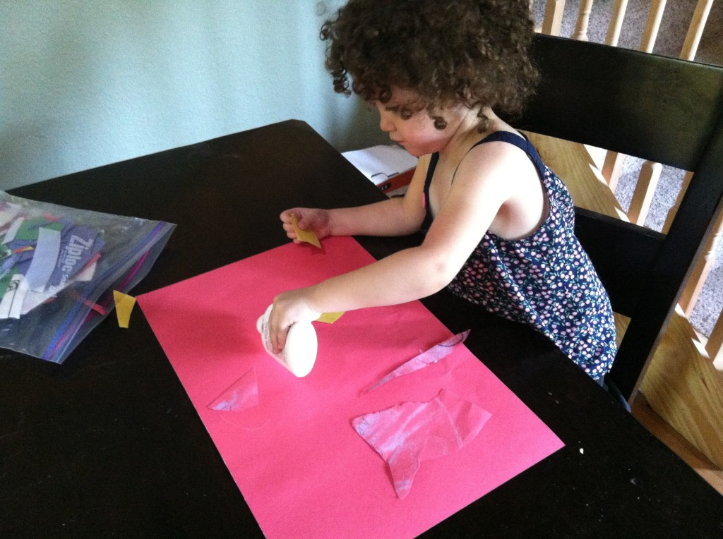 here she is putting glue down and placing random paper pieces she's cut up